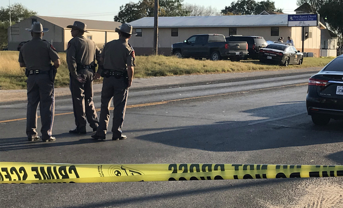 """Police block a road in Sutherland Springs, Texas, on November 5, 2017, after a mass shooting at the the First Baptist Church (rear). A gunman went into the church during Sunday morning services and shot dead some two dozen worshippers, the sheriff said, in the latest mass shooting to shock the US. """"Approximately 25 people"""" were dead, including the shooter, Wilson County Sheriff Joe Tackitt told NBC News. At least 10 people were wounded. The motive was not immediately known, he added.  / AFP PHOTO / SUZANNE CORDEIRO"""